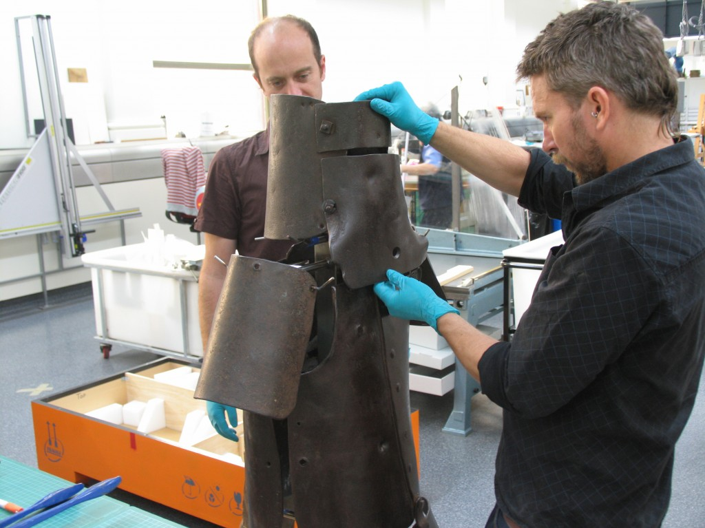 Tom Ingpen and Andrew Foster fit Ned Kelly's helmet to its display mount.