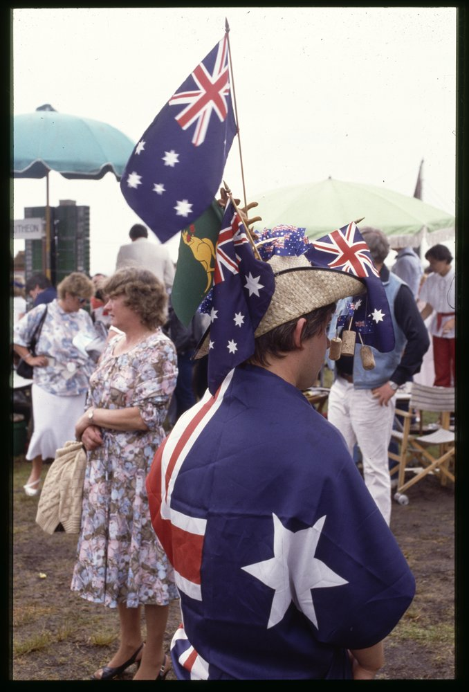 Man with Australian flag draped over his shoulders. © Rennie Ellis, 1985, courtesy of the Rennie Ellis Photographic Archive