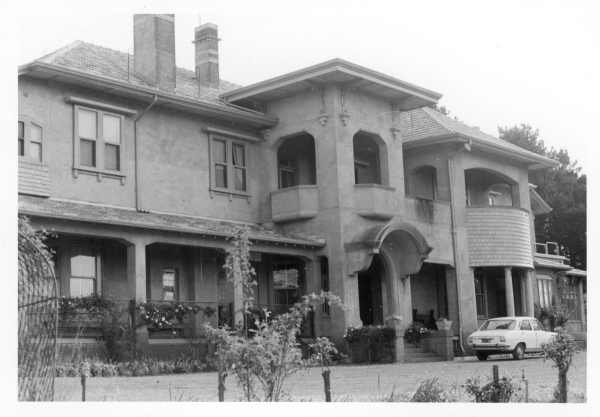 Photograph showing front exterior of large, rendered, 1920s-style house with several verandahs