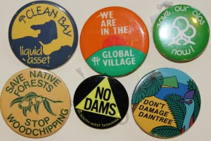 Photograph showing six round badges printed with various pro-environment slogans