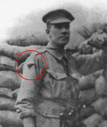 Detail from photograph showing Australian soldier standing in trench, wearing uniform; sandbags in background. Colour patch on right hand sleeve of his uniform circled in red.