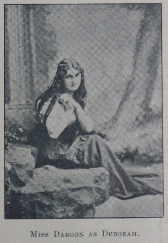 Black and white photograph of a young woman with long dark curled hair, seated on rock, clutching hands together at right shoulder