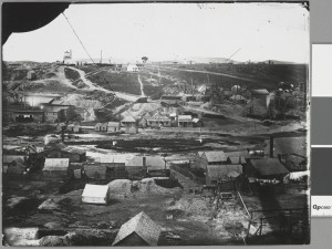 "Black and white photograph. Elevated view of goldmining settlement showing tents, wooden huts, diggings, mine shafts, derrick in distance. One building with sign ""Port Phillip Hotel""."