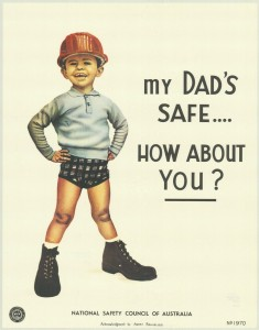 A colour image of a young boy wearing his Dad's hard hat and work boots.