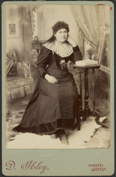 Sepia photograph showing Ned Kelly's sister Maggie Skilling. Whole-length, to left, wearing full length dress with leg-o-mutton sleeves and lace collar, seated with left elbow resting on table, left hand to cheek.