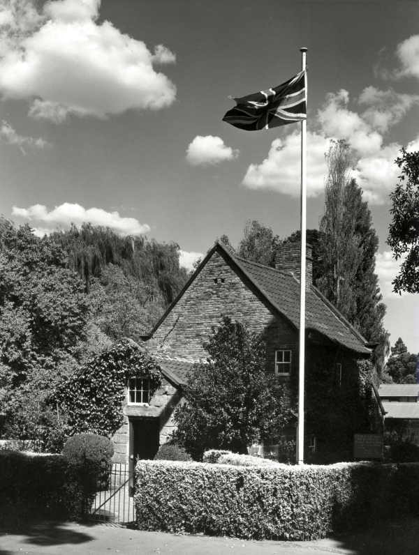 Shows the entrance to Captain Cook's Cottage, with an English flag.