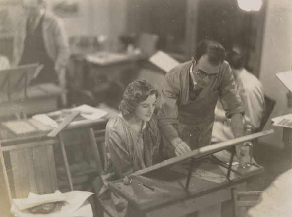Black and white photograph showing male teacher leaning over a student's drawing board, making alterations to her drawing.