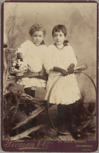 Black and white full length family studio portrait of May and Mabel Needle.