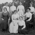 Eight women gathered on a lawn