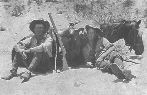 Black and white photograph of two soldiers in the desert propped up against a sitting horse. The soldiers are taking advantage of the shade provided by the horse's shadow.