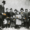 Rev Wong with children in Collingwood, holding oranges. Photographer: T. W. Cameron