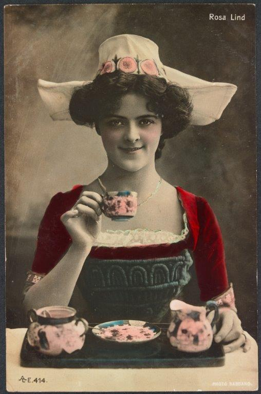 Colourised photo of young woman holding up a cup of tea as if to drink