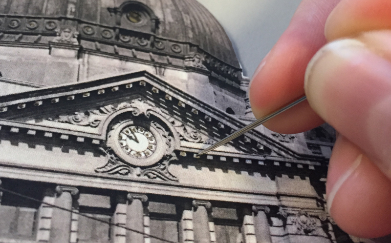 Photo of a pin being poked into paper to create small holes