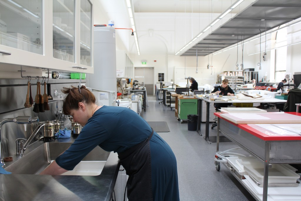 Image of a paper conservator 'washing' an ST Gill work in the conservation lab