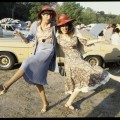 Two unidentified women kicking up their heels in carpark at racecourse © Rennie Ellis