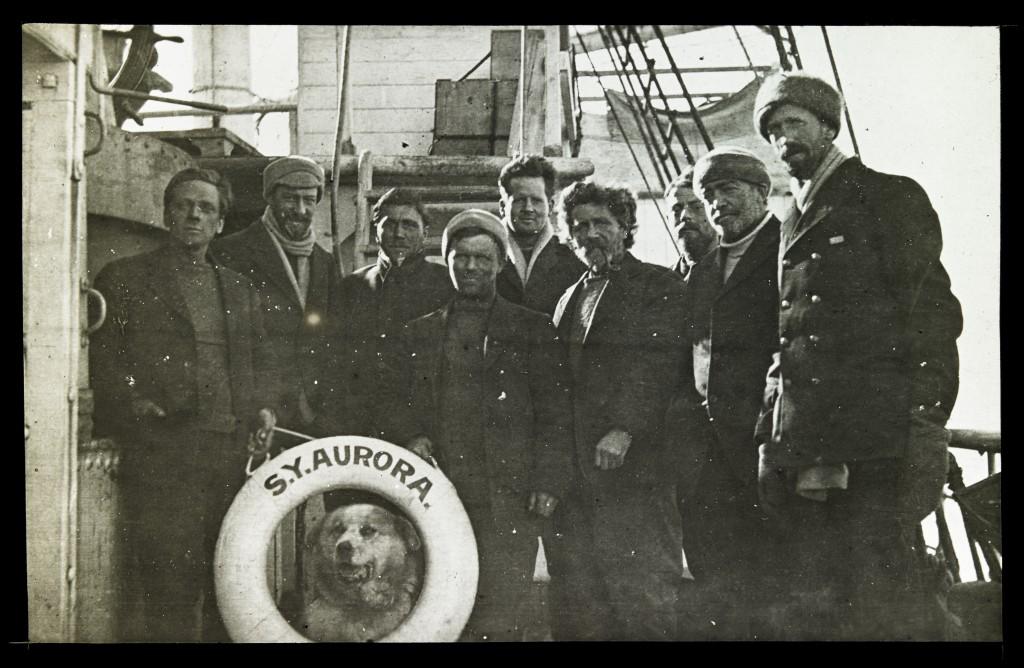 Image of crew on deck with dog and SY Aurora buoy