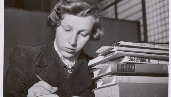 Image of a female library student writing in a notebook