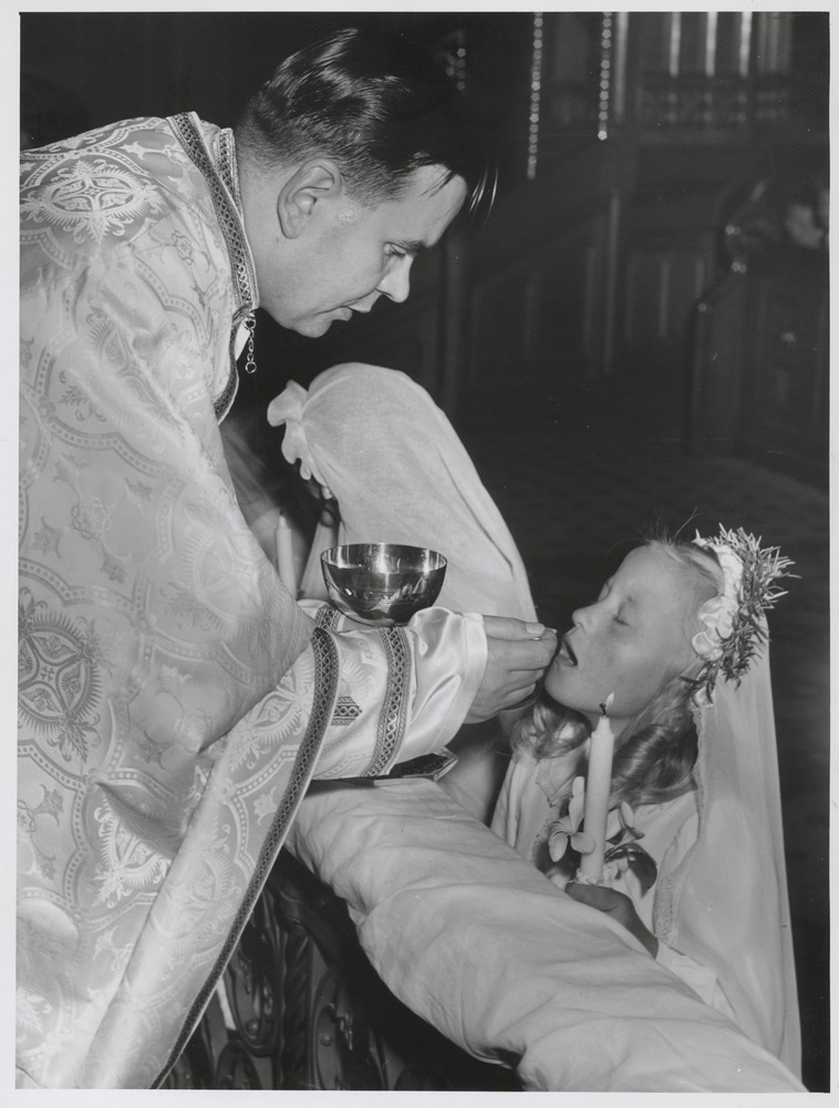 Shows Father Ivan Prasko giving Lesia Maria Pundiak her first communion at St. Patrick's Cathedral, Melbourne.
