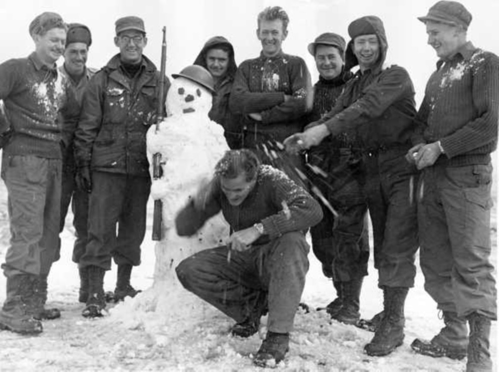 "H2002.199/3089. ""A white Christmas ... for ground crew men of No. 77 Squadron, RAAF, in Korea"". ca. 1952. Making a snowman, L-R: R.J. Page, armorer (West Ryde, Sydney, NSW), Cpl. J.E. Hainsworth, fitter IIE (Williamtown, NSW), Sgt. T.J. Yewers, fitter armorer (Alphington, Vic.), Cpl. R.C. Scott, fitter IIE (Sandwell, S. Aust.), Cpl. M.G. McKenna (Murgon, Q'ld.), LAC R.J. Milner (Turrawan, NSW), LAC S.J. Manning (Leichhardt, Sydney, NSW) and in front, LAC D.J. McKeever, flight rigger (Swanburn, W.A.)."