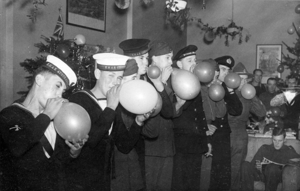 "Image H99.205/315. ""An Empire Xmas party was held at the Empire Rendezvous in London ..."". ca. 1941. Sailors from Australia, New Zealand and Holland and soldiers from Canada and New Zealand and airmen from South Africa and New Zealand, blowing up balloons at the party."
