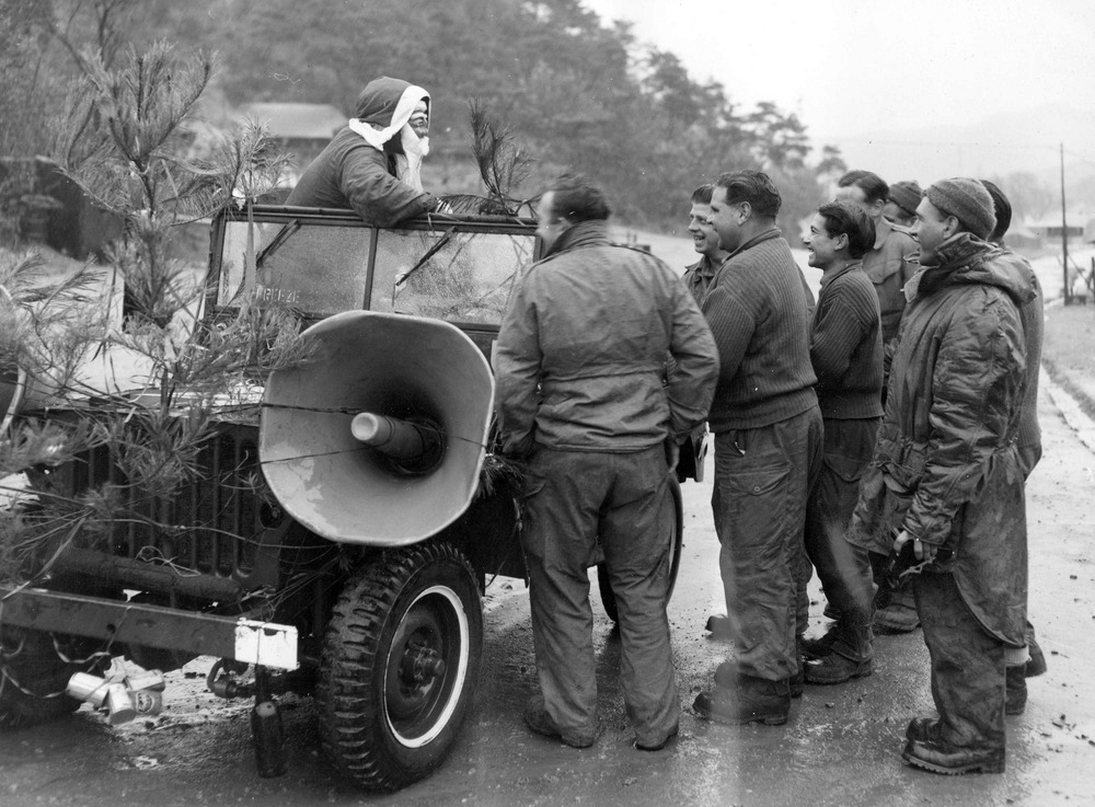 Shows Cpl. Jack Philpott from St. Kilda, Vic. dressed as Santa Claus in a jeep talking to some soldiers.