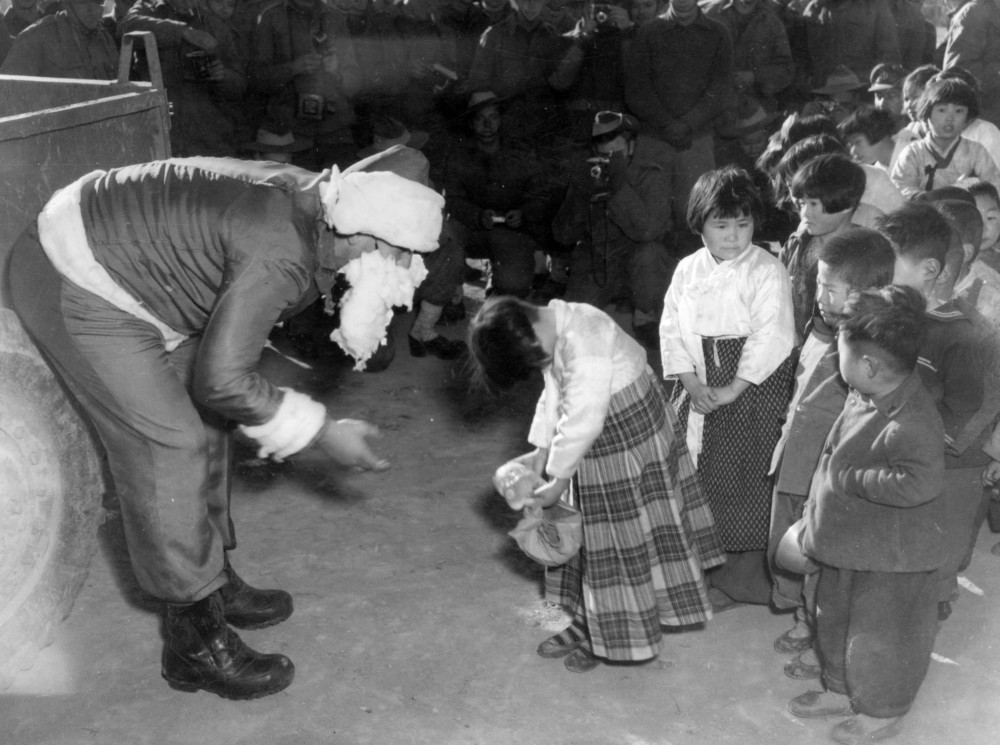Korean children receiving Christmas presents from Santa Claus of the 1 Bn Royal Australian Regiment