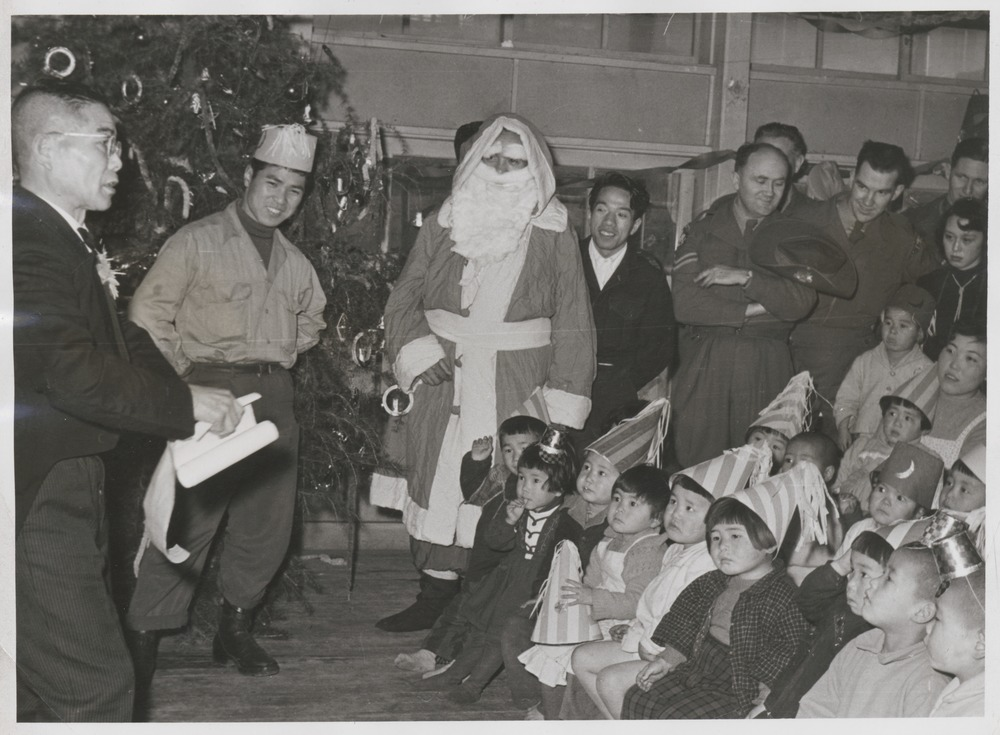 "Children seated in front of conjurer watched by soldiers and ""Santa Claus""; Pte Harry Miller (Sydney, N.S.W.) holding two children of the Futaba Hoikuen orphanage. Driver Clive Harries of the Royal Army Services Corps (British) at right hand side of image."