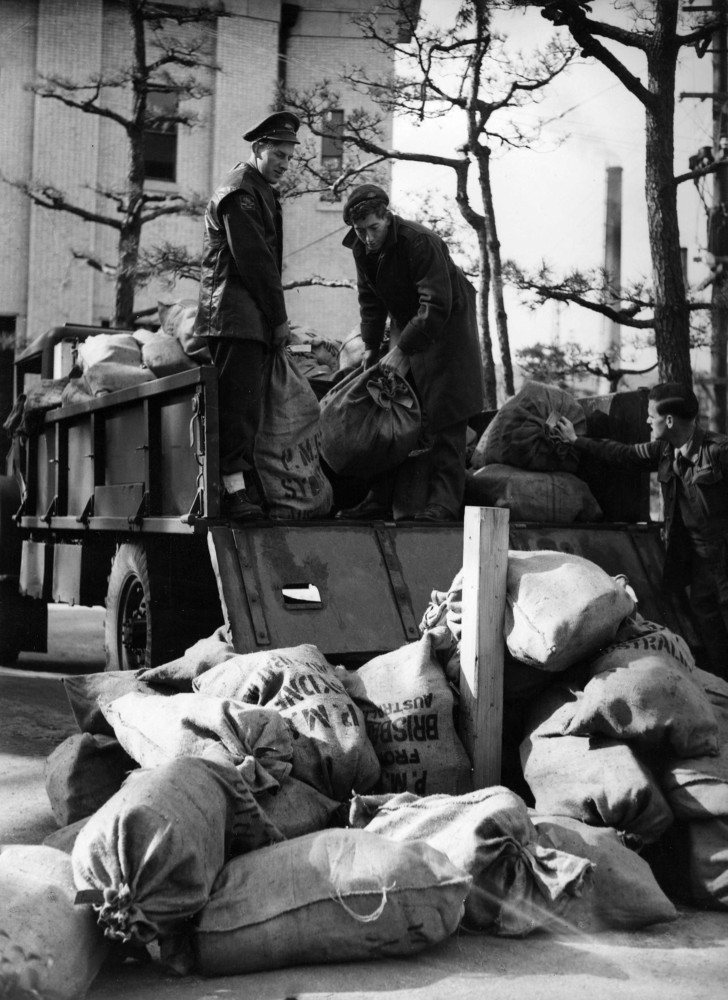 Shows mail bags being unloaded by Postal Unit members Dvr. P. Wiseman from W.A., Pte. L.R. Lloyd from N.S.W. and Sgt. E.K. Robinson from S.A.