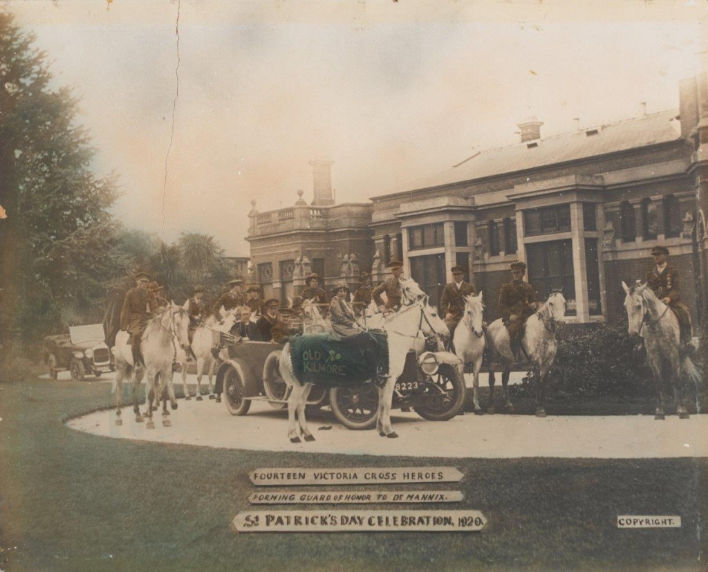 Image of several men and a young girl on white horses with a carriage in front of a building