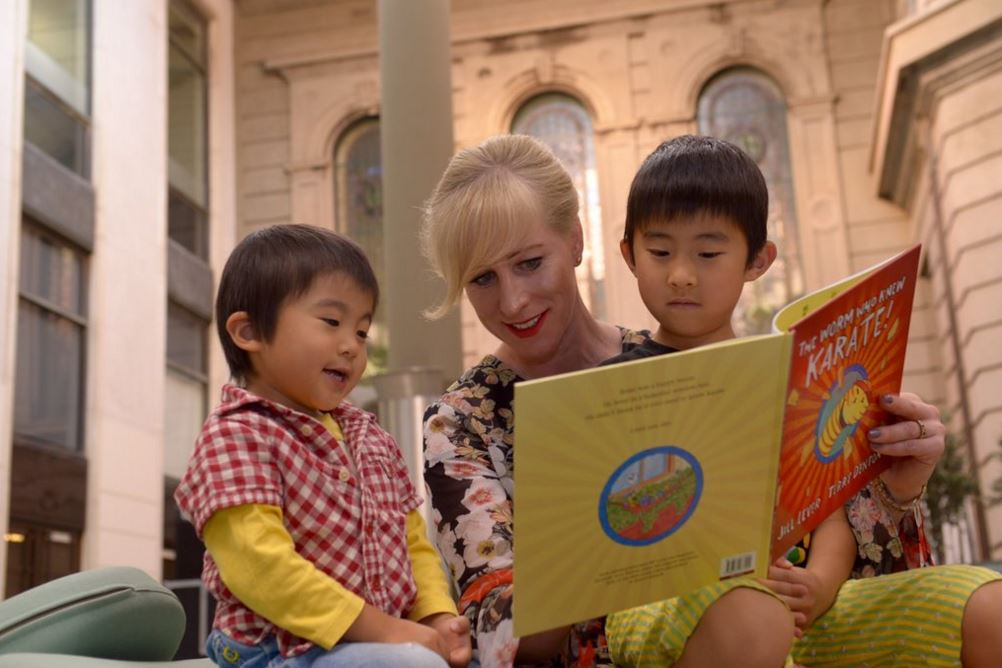 Catherine Andrews reading to two young children at Storytime