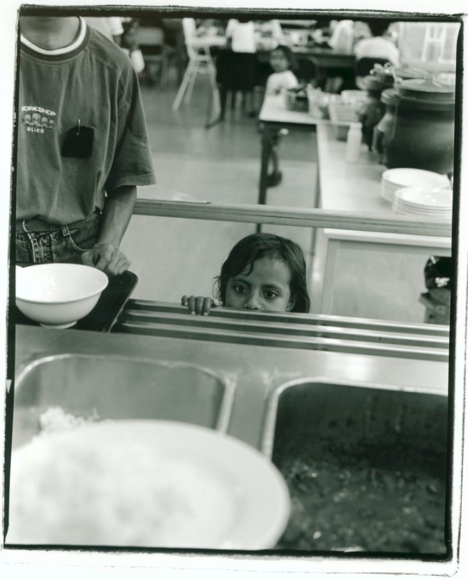 East Timorese girl looking over the edge of the food counter in the meal hall at Puckapunyal Safe Haven