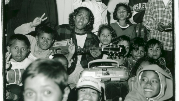 An East Timorese refugee, singing and playing the guitar, surrounded by East Timorese children at the Puckapunyal Safe Haven
