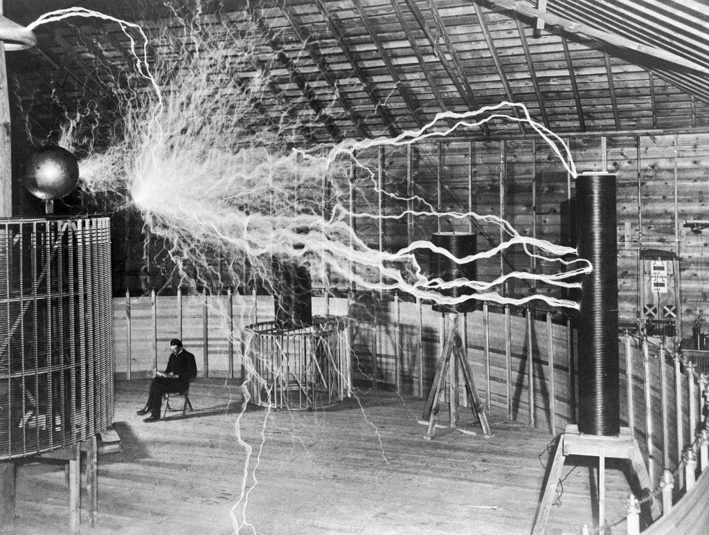 Nikola Tesla sitting with his equipment.