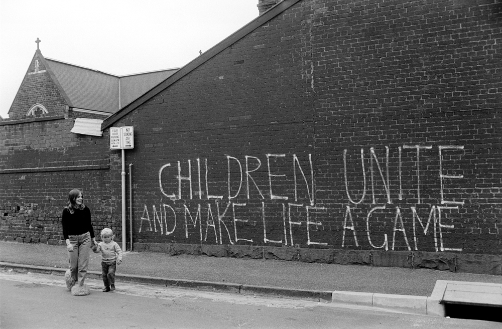 "A woman walking with a child, ""Children unite and make life a game"" painted onto a wall."