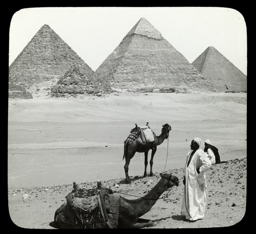 Three pyramids in the background, two people and camels in the foreground.