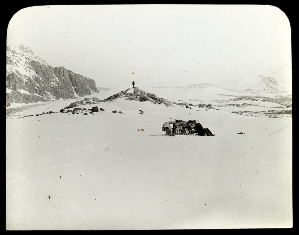 Man standing on rocky outcrop on snow-covered Antarctic landscape