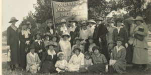 A collection of women gathered under a banner.