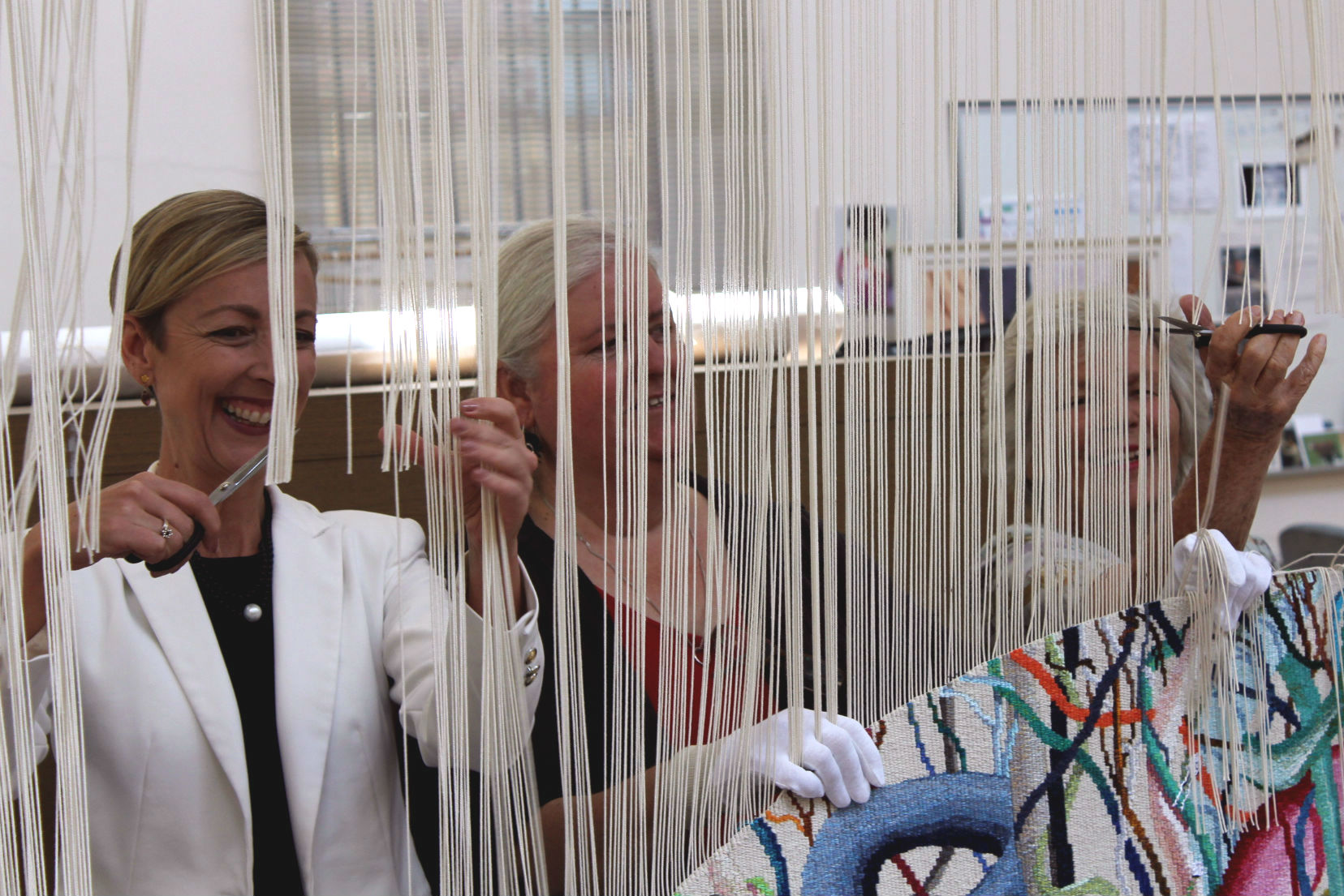 Kate Torney, State Library Victoria CEO, and Janet... cutting Gordian Knot from the loom.