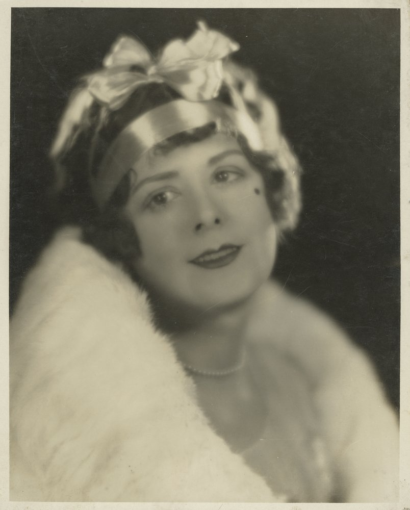 portrait of a woman in fur stole, cropped hair with bow on her head and beauty spot beneath her eye