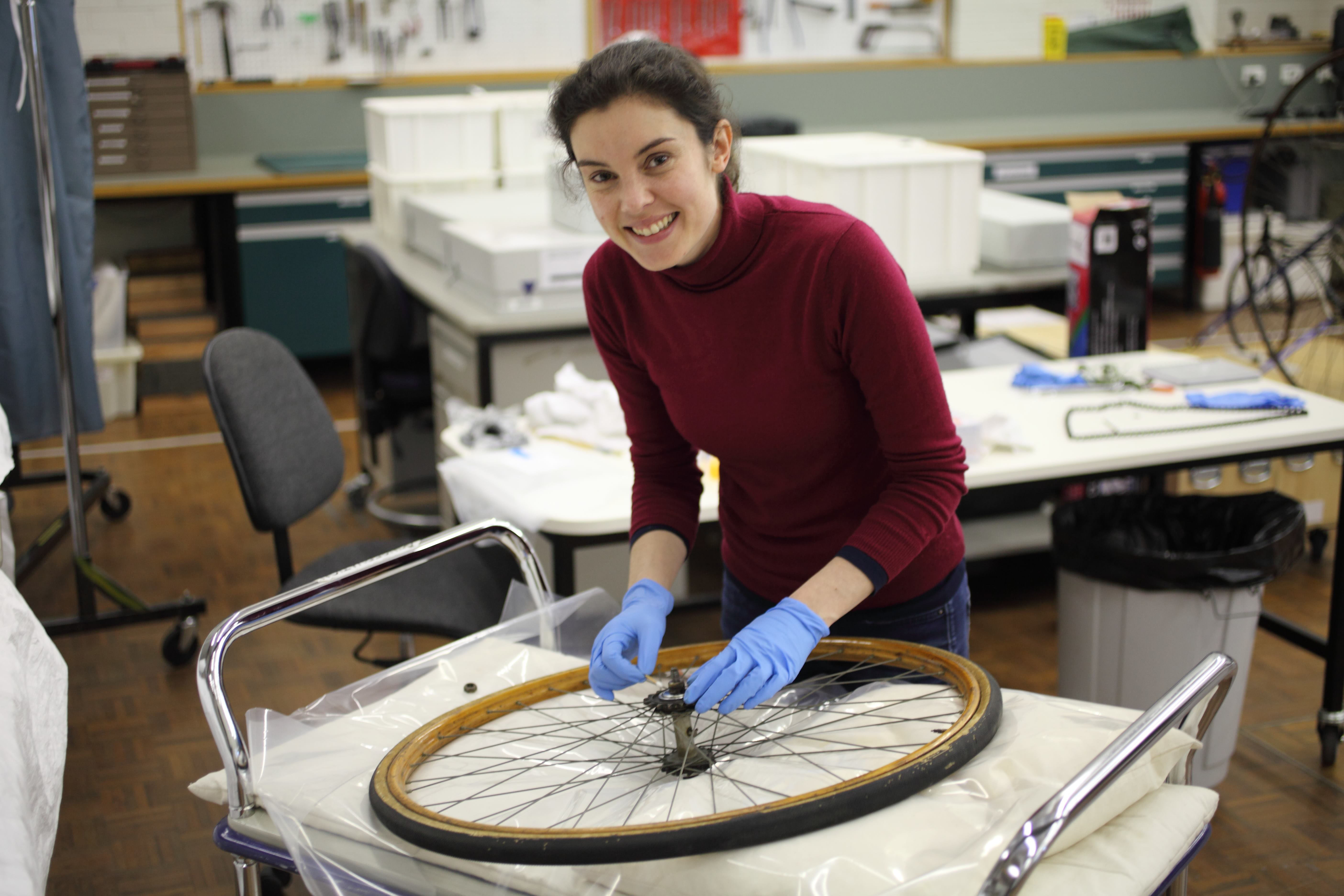 conservator wearing gloves treating a bicycle wheel