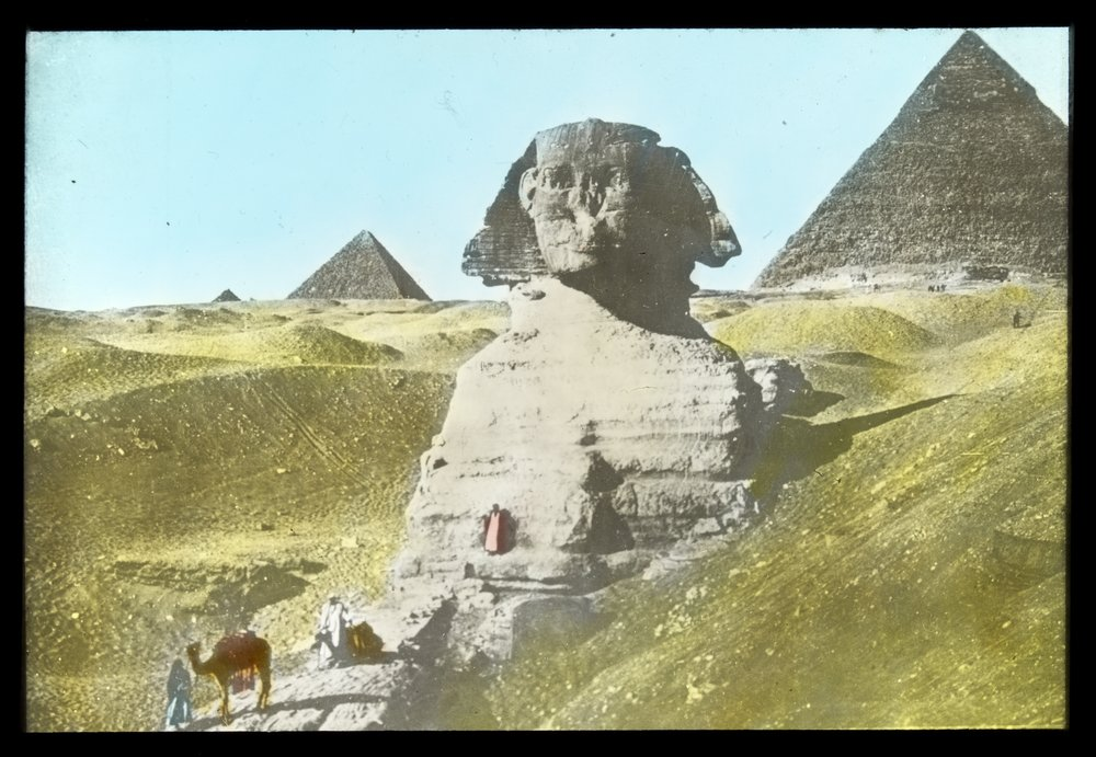 Pyramids and Sphinx and men with camels