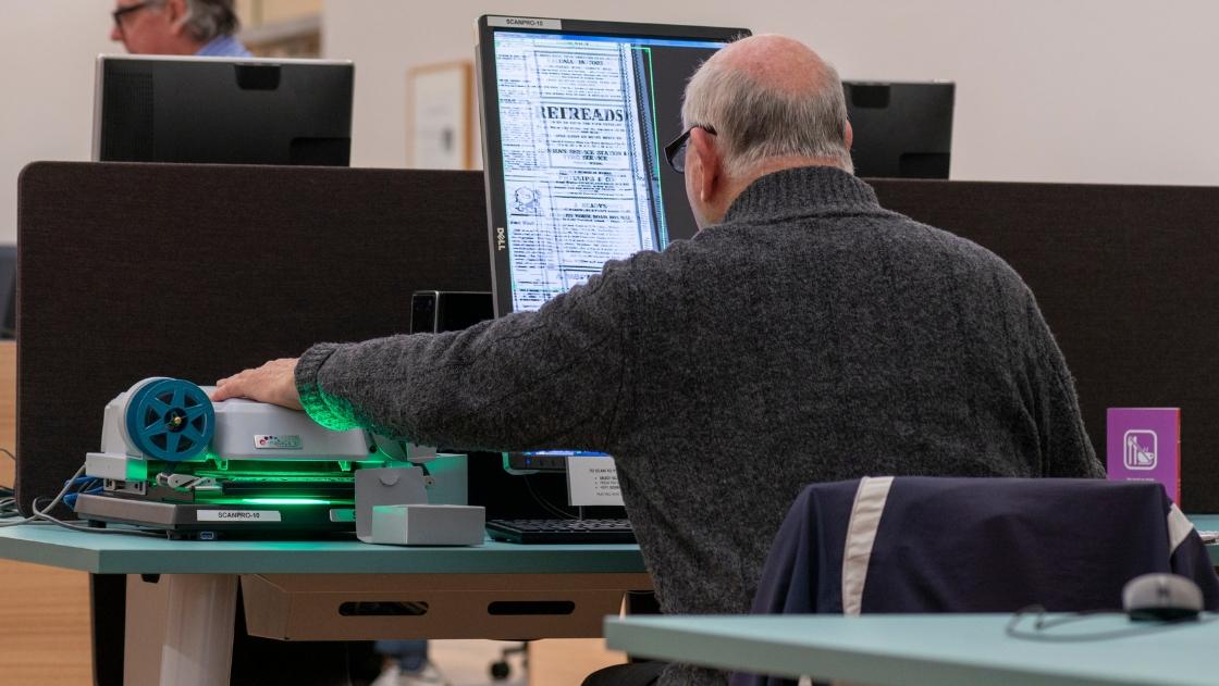 man using microfiche