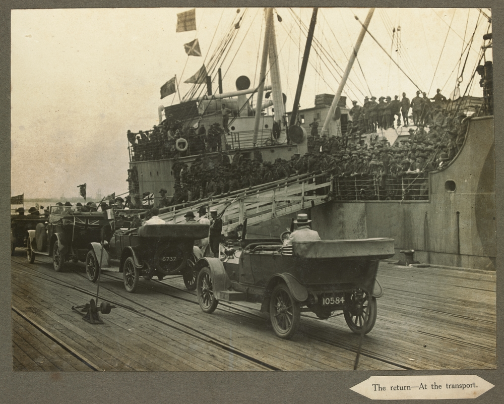 Ship moored at docks with crowd of Australian soldiers on deck and disembarking
