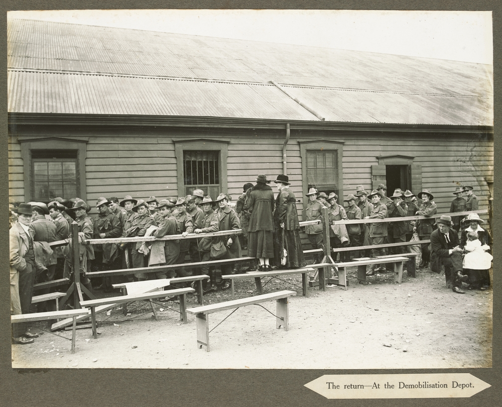 Line of soldiers standing between wooden railing fence and weatherboard barracks, two women standing on bench seats