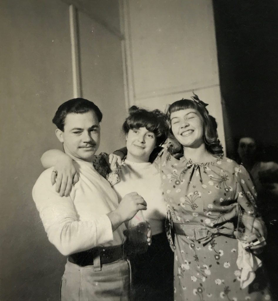 Portrait of one man and two women smiling for the camera