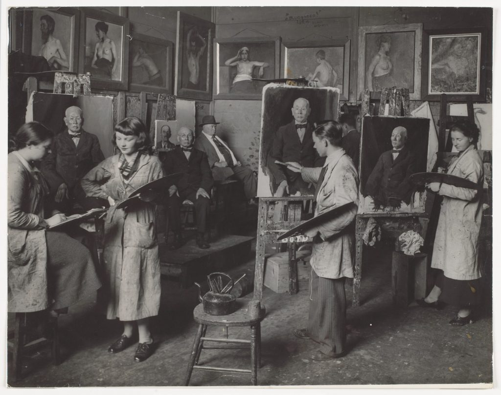 Group of men and women painting a male subject