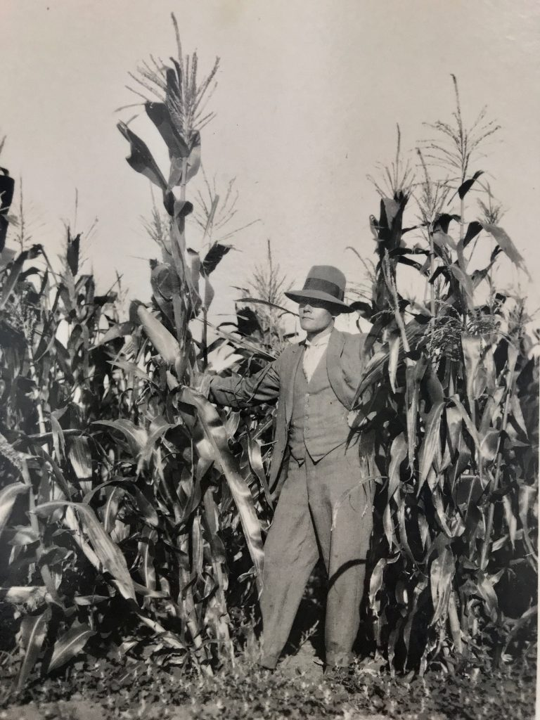 Black and white photograph of a man wearing a hat and suit standing amongs corn crops.