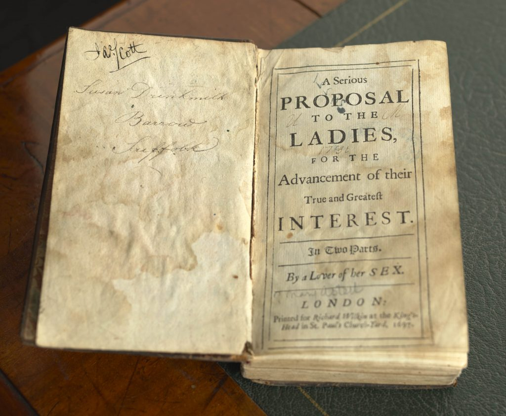 An open volume of Mary Astell's book 'A Serious Proposal to the Ladies, for the Advancement of their True and Greatest Interest', 1697, sits on a desk.