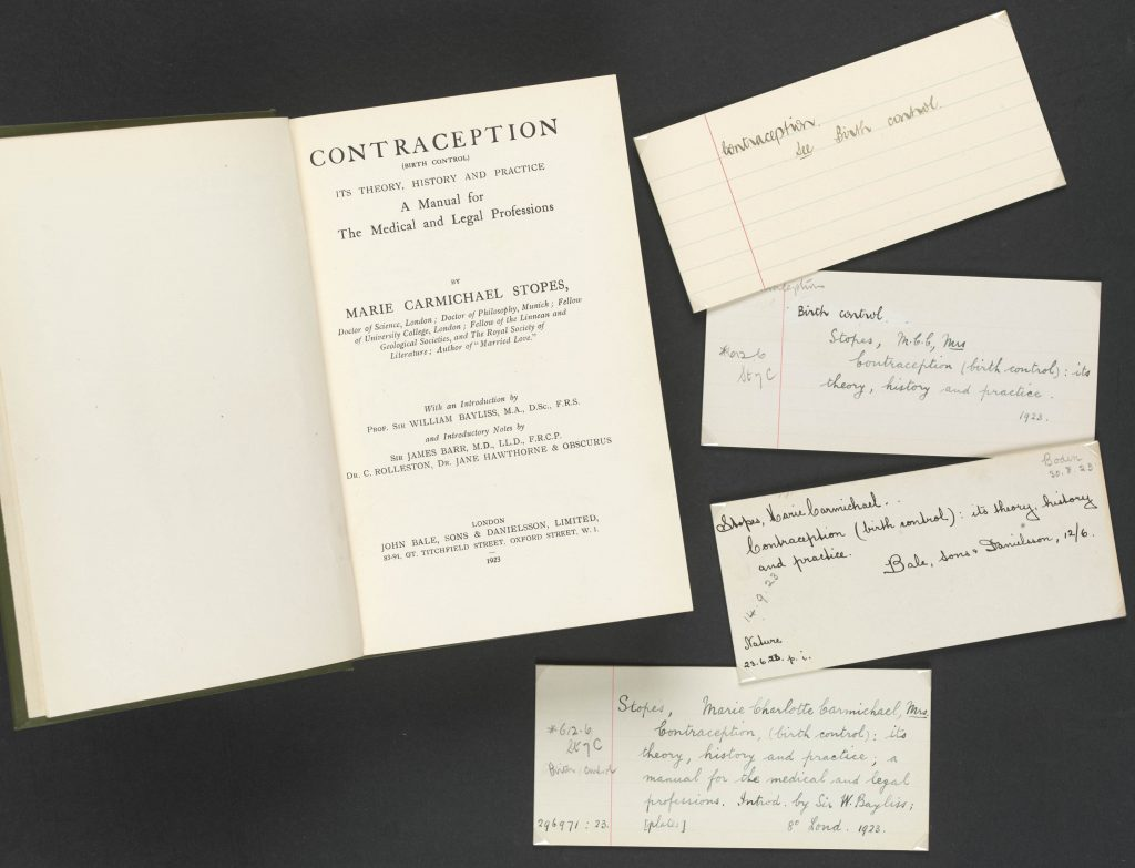 Marie Stopes' book 'Contraception' sits open at its title page, with four handwritten cataloguing cards displayed next to it.