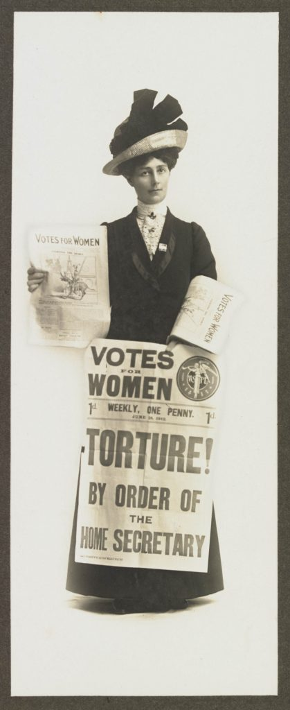 A studio portrait of Vida Goldstein selling the 'Votes for Women' newspaper.